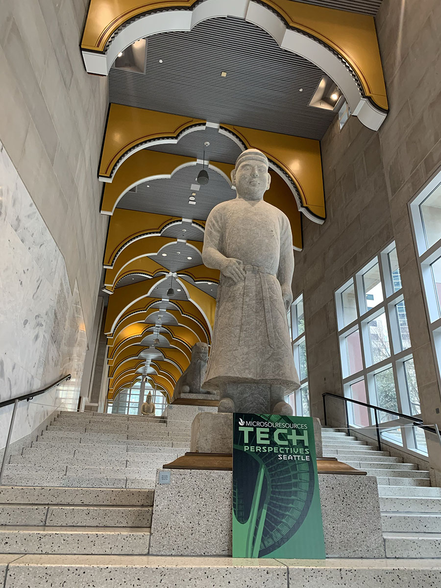 Signage for the Tech Perspectives event appears at the base of a statue in the lobby of the Seattle Art Museum.
