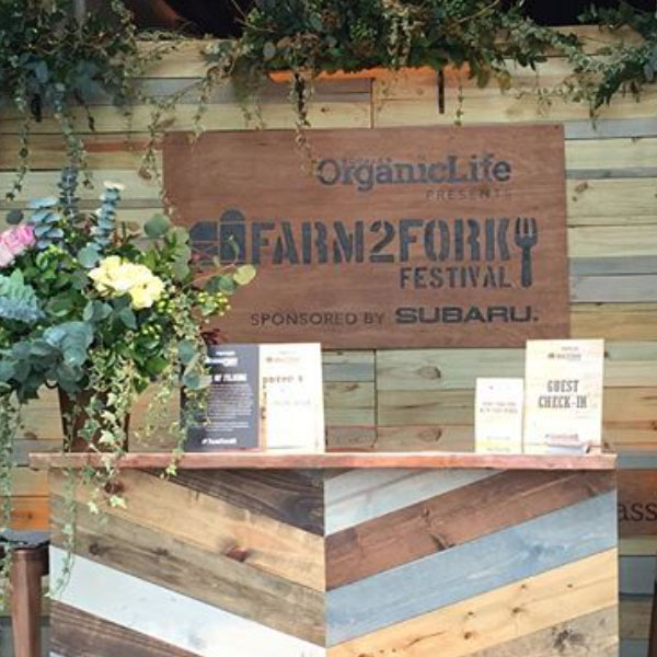 At the event the front desk area was built from reclaimed lumber and adorned with flowers and a large sign showing the event logo.
